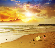 Flag in bottle on beach with sunset. A glass bottle with a small American flag on a beautiful beach with vibrant sunset in background Royalty Free Stock Photos