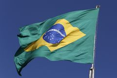 Flag of Brazil fluttering in the wind. Under a sky of intense blue stock photography