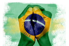 Flag of Brazil and number 2016. Closeup of the hands of a young man put together patterned with the flag of Brazil and the number 2016 Royalty Free Stock Images
