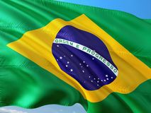 Flag of Brazil waving in the wind against deep blue sky. High quality fabric.  stock images