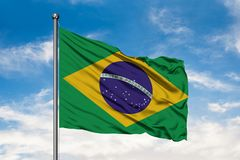 Flag of Brazil waving in the wind against white cloudy blue sky. Brazilian flag stock images