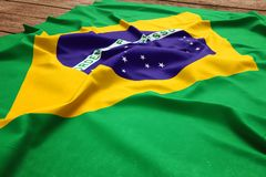 Flag of Brazil on a wooden desk background. Silk Brazilian flag top view.  royalty free stock photography