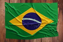Flag of Brazil on a wooden table background. Wrinkled Brazilian flag top view.  royalty free stock image