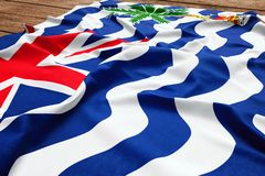 Flag of British Indian Ocean Territory on a wooden desk background. Silk flag top view.  royalty free stock photography