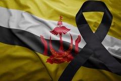 Flag of brunei with black mourning ribbon. Waving national flag of brunei with black mourning ribbon Royalty Free Stock Image