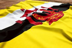 Flag of Brunei on a wooden desk background. Silk Bruneian flag top view.  stock photography