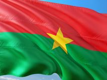 Flag of Burkina Faso waving in the wind against deep blue sky. High quality fabric.  stock photos