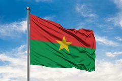 Flag of Burkina Faso waving in the wind against white cloudy blue sky. Burkinese flag.  stock image