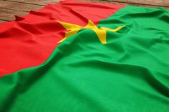 Flag of Burkina Faso on a wooden desk background. Silk Burkinabe flag top view.  stock photo