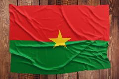Flag of Burkina Faso on a wooden table background. Wrinkled Burkinabe flag top view.  royalty free stock photo