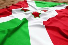 Flag of Burundi on a wooden desk background. Silk Burundian flag top view.  stock image