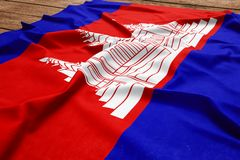 Flag of Cambodia on a wooden desk background. Silk Cambodian flag top view.  stock image