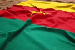 Flag of Cameroon on a wooden desk background. Silk Cameroonian flag top view.  stock photography