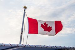 Canadian flag flying on the wind in front of the bright cloudy sky. Flag of Canada flying on a boat flagpole in a sunny summer daylight Royalty Free Stock Image