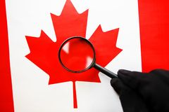 The flag of CANADA looks through a magnifying glass. Study of the history and culture and people of the country of Canada. The. Concept of studying the royalty free stock image