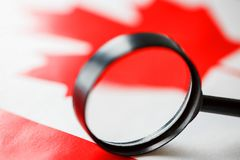 The flag of CANADA looks through a magnifying glass. Study of the history and culture and people of the country of Canada. The. Concept of studying the royalty free stock photography