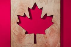 A flag of Canada, a maple leaf carved from a tree on a brightly red background royalty free stock images