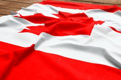 Flag of Canada on a wooden desk background. Silk Canadian flag top view.  royalty free stock images