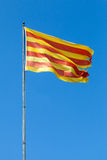 Flag of Catalonia above blue sky Royalty Free Stock Photos