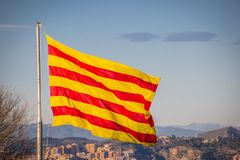 Flag of Catalonia. Sanyor flies over Barcelona.  stock image