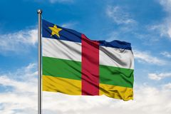 Flag of Central African Republic waving in the wind against white cloudy blue sky.  royalty free stock photography