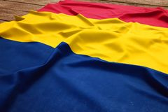 Flag of Chad on a wooden desk background. Silk Chadian flag top view.  royalty free stock image