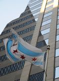 Flag of Chicago. A view of a flag of the city of Chicago, waving in the wind in front of a commercial building Royalty Free Stock Photography