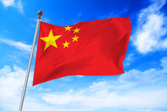 Flag of China developing against a blue sky. Flag of China developing against a clear blue sky Royalty Free Stock Images