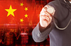 Flag of China downtrend stock data diagram with businessman holding a stethoscope Stock Image
