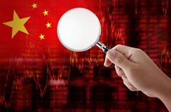 Flag of China downtrend stock data diagram with hand holding magnifying Stock Images