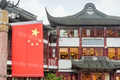 The Flag of China at the Old City of Shanghai. The Flag of China on street at the Old City of Shanghai. Scenic traditional Chinese building is visible in royalty free stock photography