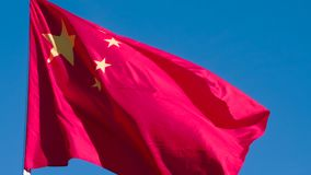 Flag of China is slowly flying. The Big State Flag is illuminated by the sun and flutters epically in the wind against the rising sun. Slow Motion 120 fps stock video