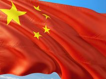 Flag of China waving in the wind against deep blue sky. High quality fabric stock photo