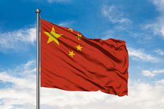 Flag of China waving in the wind against white cloudy blue sky. Chinese flag.  stock photo