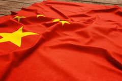 Flag of China on a wooden desk background. Silk Chinese flag top view.  stock photography