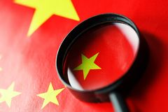 The flag of the CHINESE PEOPLE`S REPUBLIC is looking through a magnifying glass. The study of the history and culture of a large royalty free stock image