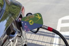 Flag of Christmas Island on the car`s fuel filler flap. Flag of Christmas Island on the car`s fuel tank filler flap. Fueling car with petrol pump at a gas Royalty Free Stock Photos