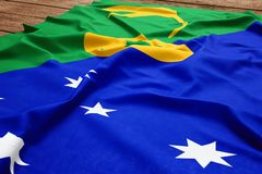 Flag of Christmas Islands on a wooden desk background. Silk flag top view stock images