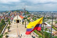 Flag and Church in Guayaquil. Ecuadorian flag on top of Santa Ana hill with a church and the city of Guayaquil visible in the background in Ecuador Stock Images
