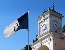 Flag of  the city of Udine with the ancient tower clock in Libertà square on background.  stock photography