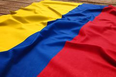Flag of Colombia on a wooden desk background. Silk Colombian flag top view.  royalty free stock photo