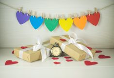 St Valentine`s Day, gifts with white bows. Flag of colorful hearts. Gifts with white bows and watch that marks the time to love Royalty Free Stock Images