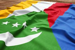 Flag of Comoros on a wooden desk background. Silk Comoran flag top view.  royalty free stock images