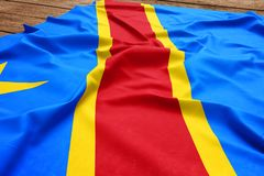 Flag of Congo on a wooden desk background. Silk Congolese flag top view.  royalty free stock image