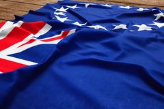 Flag of Cook Island on a wooden desk background. Silk flag top view.  royalty free stock photos