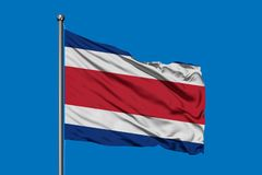 Flag of Costa Rica waving in the wind against deep blue sky. Costa Rican flag royalty free stock photography