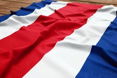 Flag of Costa Rica on a wooden desk background. Silk Costa Rican flag top view.  stock images