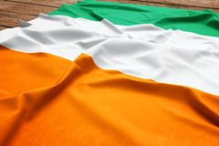Flag of Cote d`Ivoire on a wooden desk background. Silk Ivorian flag top view.  stock photography