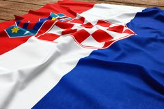 Flag of Croatia on a wooden desk background. Silk Croatian flag top view.  royalty free stock images