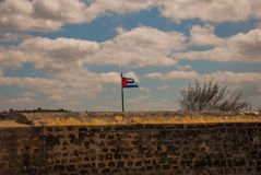 Flag of Cuba against the sky at the fortress wall. The old colonial castle of San Salvador de la Punta. Havana. Cuba.  Stock Photography